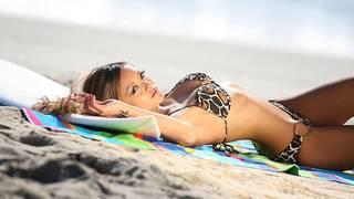A menina asiática na praia.